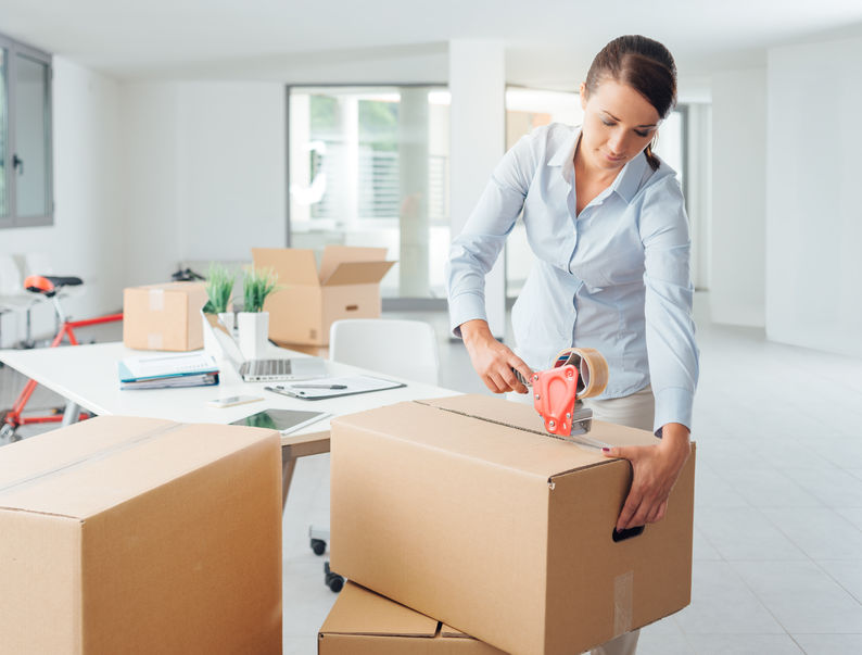 young business woman taping up a cardboard box in the office, relocation and new business concept